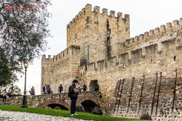 O Castelo de São Jorge em Lisboa do lado de fora, com enormes torres feitas de pedras amareladas, uma ponte por cima de um antigo fosso gramado por onde algumas pessoas passam e árvores. Um homem de preto lê um mapa em frente ao castelo.