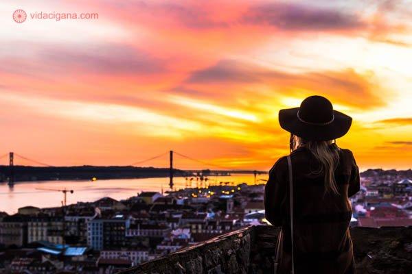 Uma mulher usando um chapéu observa a capital de Portugal do alto do Castelo de São Jorge, em Lisboa. O céu está lindíssimo com suas cores que vão do amarelo ao roxo, passando por rosa e laranja. O rio Tejo também está ao fundo juntamente com a cidade.