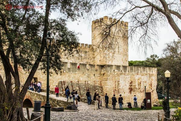 O Castelo de São Jorge em Lisboa visto de sua entrada em meio a árvores. Muitas pessoas estão passando em sua frente.