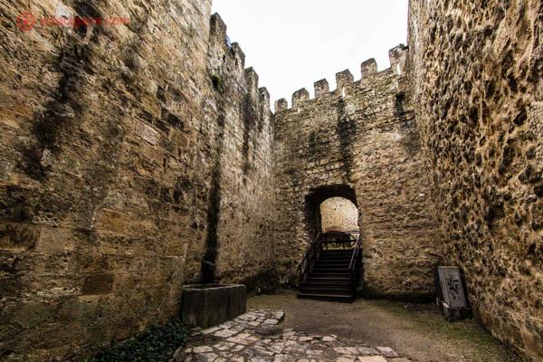 O Castelo de São Jorge em Lisboa com suas muralhas altas de pedras amareladas, uma pequena porta com uma escada de madeira.