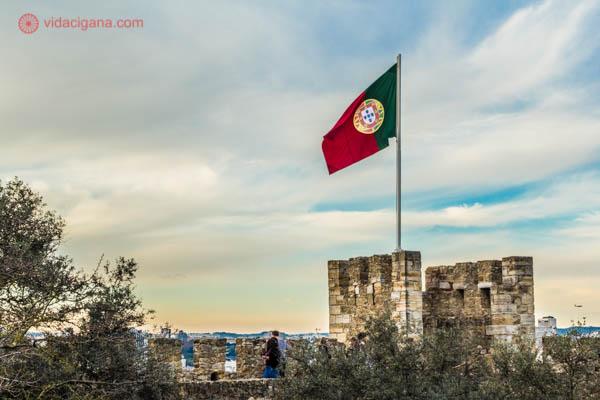 A bandeira de Portugal com suas cores vermelha e verde tremula no topo da mais alta torre do Castelo de São Jorge em Lisboa. O céu possui muitas nuvens e alguns pontos azuis. Árvores se encontram a frente do castelo.