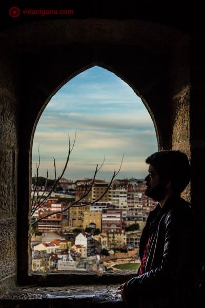 A silhueta de um homem sentado em uma janela do castelo de são jorge em Lisboa, vendo a cidade lá ao fundo. O céu está azul e as casas são coloridas.