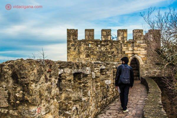 Um homem de preto caminhando pela muralha do Castelo de São Jorge em Lisboa. O céu está azul com algumas nuvens brancas, o castelo é feito de pedras amareladas.