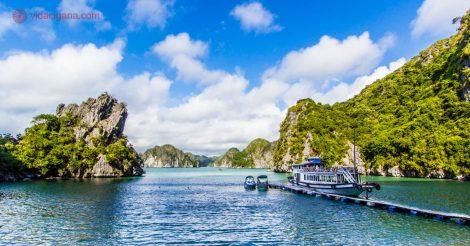 Halong Bay, no Vietnã, com suas lindas ilhas cheias de verde, suas águas mornas verdes, e seu céu azul. Com um barco ancorado e dois barquinhos amarrados em seu pier. Tudo o que você precisa saber sobre o clima no Vietnã e a melhor época para se visitar o país