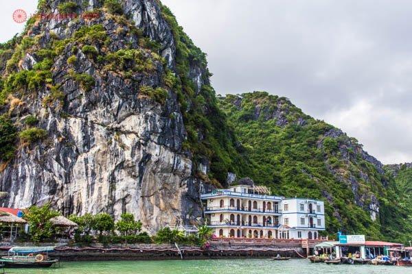 O porto de entrada para Halong Bay, no Vietnã, com suas montanhas altas e verdes, casinhas em suas margens de águas verdes. O céu está nublado.