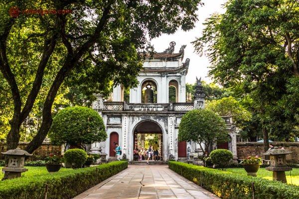 O Templo da Literatura no Vietnã, com sua arquitetura oriental, com paredes brancas e o telhado encurvado em suas pontas. Um caminho leva até o templo, com muitas árvores ao redor.