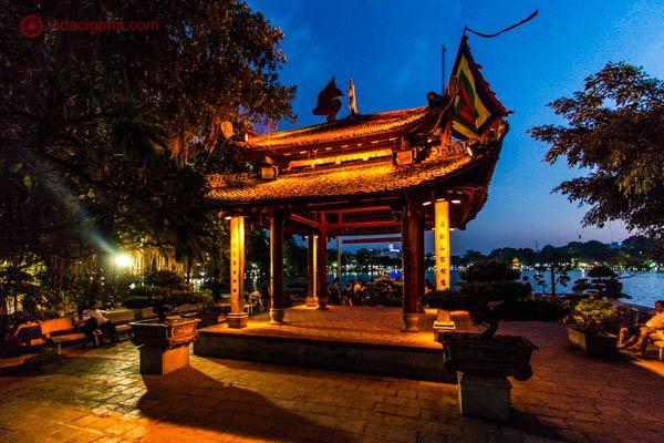 Um templo iluminado no Vietnã, feito de madeira escura. A foto foi tirada a noite e o templo está iluminado com luzes amarelas.