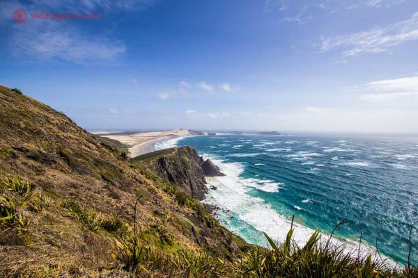 A Ninety Mile Beach, na Ilha Norte da Nova Zelândia, durante o verão, com suas águas azuis, suas areias brancas e montanhas verdes perto do mar.