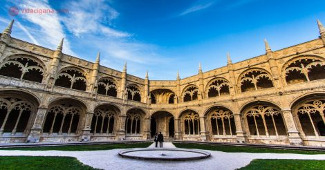 O pátio principal do Mosteiro dos Jerônimos em Lisboa, com suas varandas brancas e lindas, cheias de adorno. A foto foi tirada durante o pôr do sol, com as paredes alaranjadas. Um casal está parado na frente do prédio de arquitetura manuelina. O céu está azul com algumas poucas nuvens brancas.