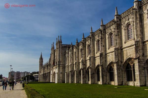 A fachada do Mosteiro dos Jerônimos em Lisboa com suas paredes altamente adornadas de pedras brancas. Em sua frente um gramado verde e aparado e o céu azul.