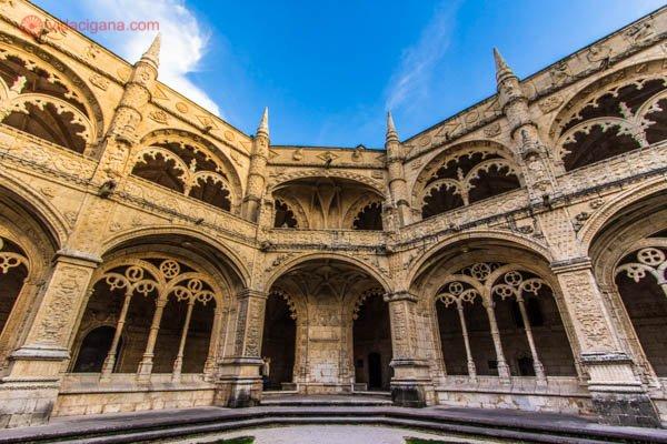 O pátio do Mosteiro dos Jerônimos em Lisboa, com suas paredes brancas completamente adornadas. A foto foi tirada no pôr do sol. O céu está azul.