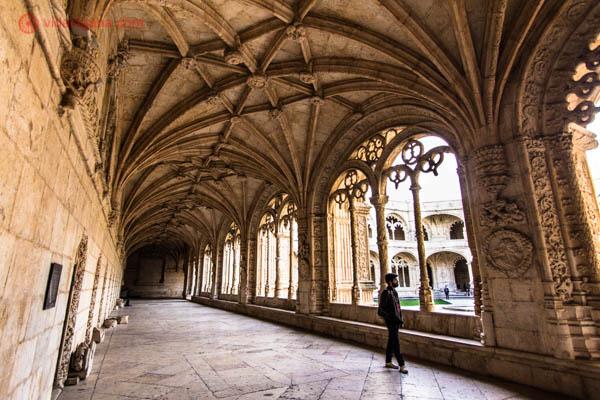 O Mosteiro dos Jerônimos em Lisboa, com seus tetos abobadados em pedra branca, totalmente adornado. Um homem anda por seus corredores.