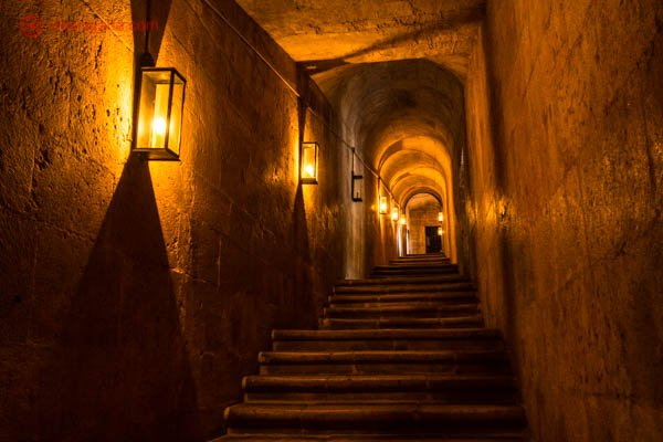 Por dentro do Mosteiro dos Jerônimos em Lisboa, com suas escadas de pedra e paredes sem janelas, deixando o ambiente bastante escuro, com luzes em suas paredes de tons amarelos.