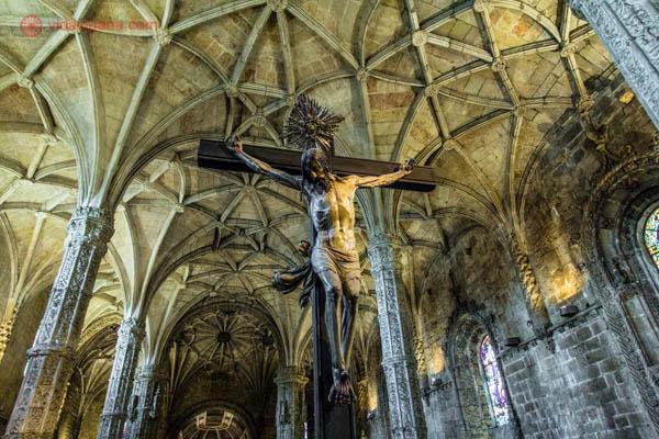 O interior da igreja do Mosteiro dos Jerônimos em Lisboa, com um enorme cruxifico em seu meio. O teto é todo abobadado, em branco.