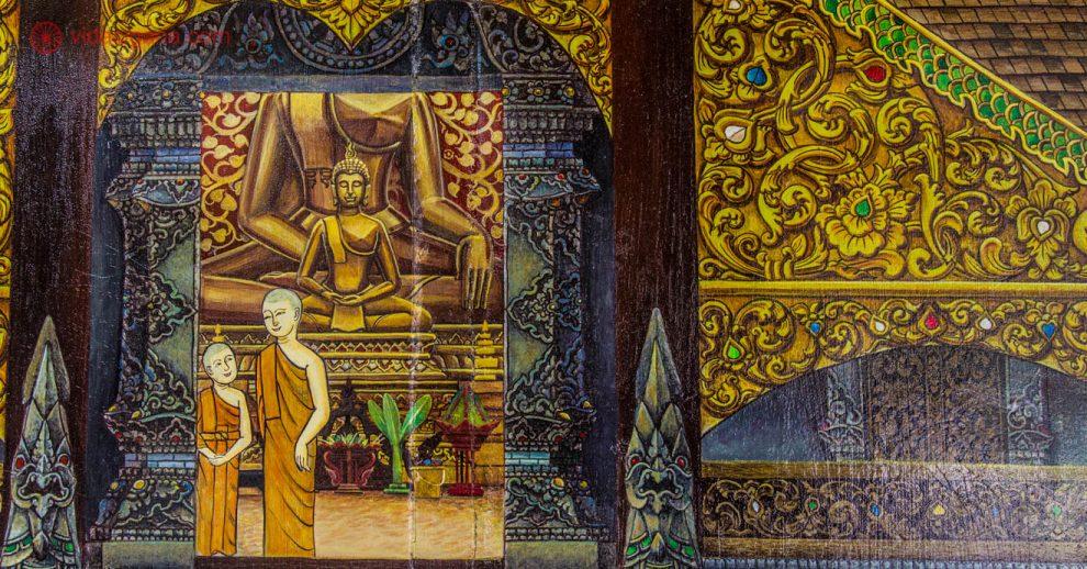 Um mural na parede em Chiang Mai onde dois monges estão pintados em formato de desenho, uma criança e um adulto, na entrada de um templo budista, com uma imagem de buda no interior.