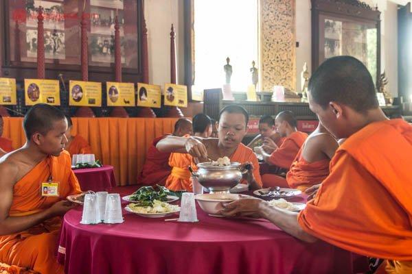 Monges budistas almoçando dentro de um templo em Chiang Mai, na Tailândia. Eles vestem túnicas laranjas, estão sentados no chão e dividem uma panela de arroz. A iluminação está contraluz.