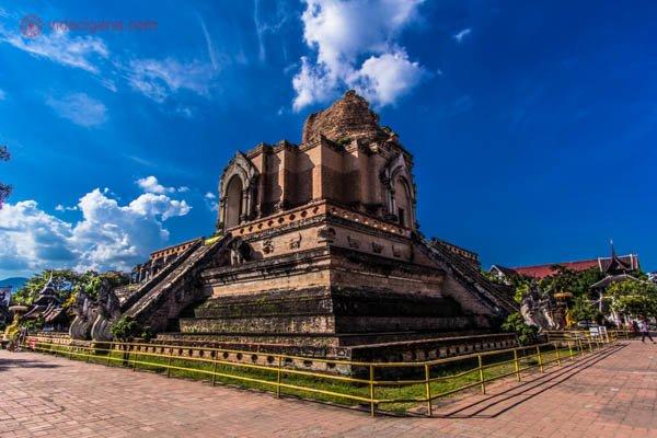 As ruínas de um templo em Chiang Mai, na Tailândia. Ele fica numa região central, com parte dele destruída. O céu está azul e tem um pouco de grama bem ao redor do templo. Ele é gradeado para ninguém conseguir passar.