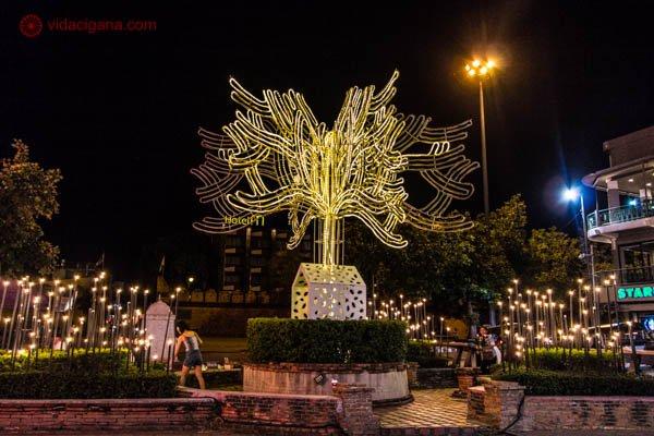 Uma árvore feita de luz led na saída do portão da cidade antiga de Chiang Mai, na Tailândia. A árvore dá um tom moderno a cidade, está na cor amarelo e repleta de outras luzes e alguns hoteis.