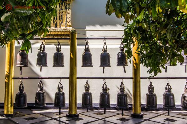 Vários sinos pendurados em um templo em Chiang Mai, na Tailândia. Eles estão em duas filas, uns em cima dos outros, com árvores emoldurando a foto.