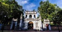 Um prédio histórico em Hanói na entrada do Templo da Literatura na capital do Vietnã. Ele possui arquitetura oriental, com as quinas curvadas para cima, é um prédio branco e pequeno que hoje mais serve como pórtico. A sua frente árvores com folhas verdes fazem sombra para quem passa. O céu está azul.