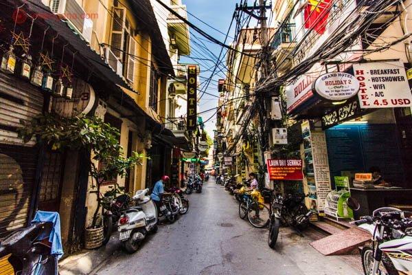 Onde ficar em Hanoi: Uma rua no Old Quarter em Hanói, no Vietnã com várias casas de dois andares, fios e mais fios elétricos, motos estacionadas e uma via estreita para passar automóveis. Caótico.