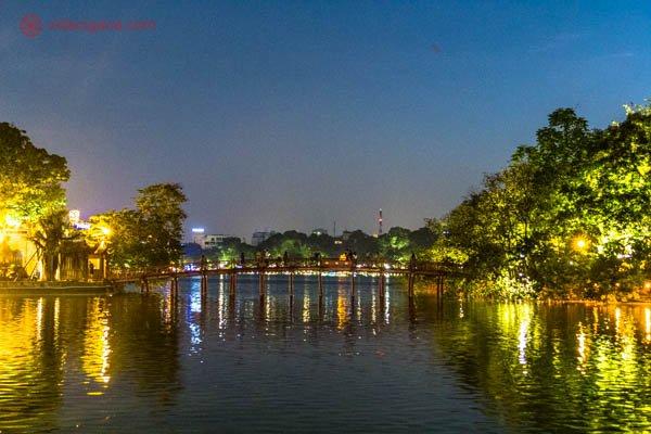 Uma ponte no estilo oriental na cor vermelha em cima do lago mais famoso de Hanói, no Vietnã. As luzes estão todas acesas, com várias árvores ao redor. A foto foi tirada a noite.