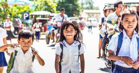 três crianças, duas meninas e um menino cambojanos andando pelas ruas de Phnom Penh, a capital do Camboja. eles voltam da escola pois estão os treês uniformizados. os três sorriem para a câmera.
