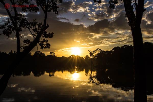 O pôr do sol em Angkor, no Camboja. O sol está se pondo atrás das árvores e na frente do lago. Muitas nuvens e o céu está azul e amarelo.