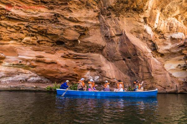 Um barquinho azul e branco com várias pessoas dentro usando coletes salva vidas laranjas estão navegando pelo cânion do xingó, no rio são francisco.