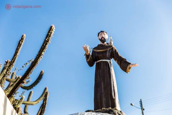 Uma estátua de São Francisco de Assis em cima de um monte, com uma pomba em seu ombro. O céu está azul e tem alguns cactos no canto da foto.