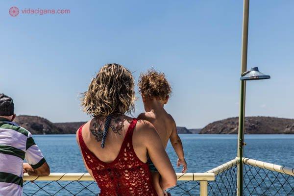 Uma mulher loira vestindo uma roupa de praia vermelha segura um menino no colo. Eles estão a bordo de um catamarã no cânion do xingó, no rio são francisco, entre alagoas e sergipe. O céu está azul, a água também e ao longe é possível ver as paredes do cânion.