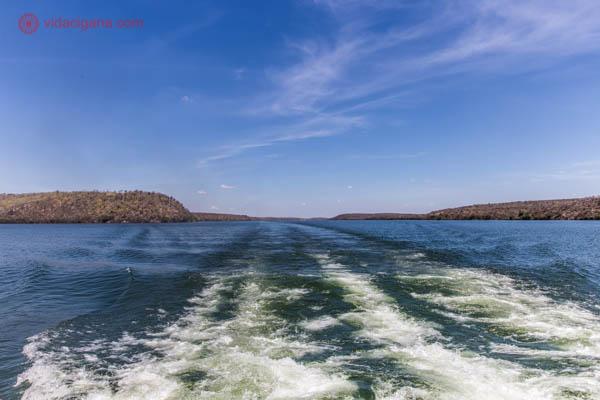 O rio são francisco no cânion do xingó, com suas águas azuis e seus paredões ao fundo de cor alaranjada. Na água o trajeto do barco. O céu está azul.