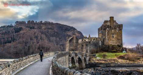 O castelo eilean donan, nos highlands da escócia, cercado por 3 lochs e por montanhas nevadas. Um homem caminha com um schnauzer branco em direção ao castelo. Está anoitecendo e um pequeno por do sol pode ser visto em meio as nuvens.