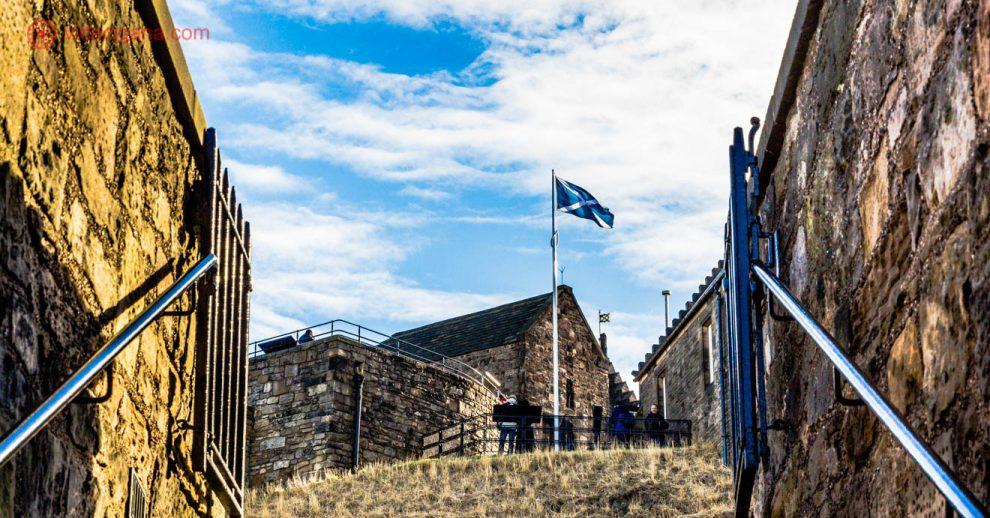 Vista de um ângulo do Castelo de Edimburgo, um dos castelos na Escócia, o mais famoso deles. Fica na cidade de Edimburgo, a mais visitada do país. A foto foi tirada de uma das escadas externas do castelo, de onde é possível ver a bandeira da Escócia balançando no vento, nas cores azul e branca. Ao redor dela, vários outros complexos do castelo. O céu está azul com nuvens brancas.