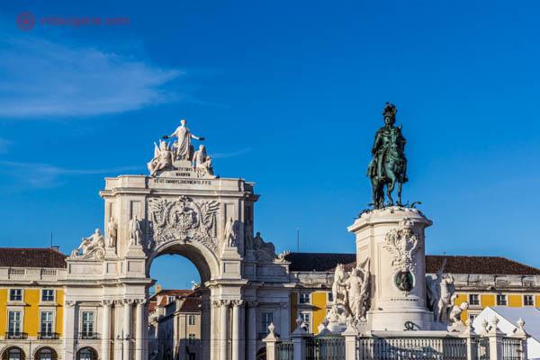 O que fazer em Lisboa: A Praça do Comércio com uma estátua equestre de D. José I em seu meio. Ao fundo, o Arco Triunfal da Rua Augusta. A praça é cercada de prédios amarelos. A foto foi tirada num lindo dia ensolarado.