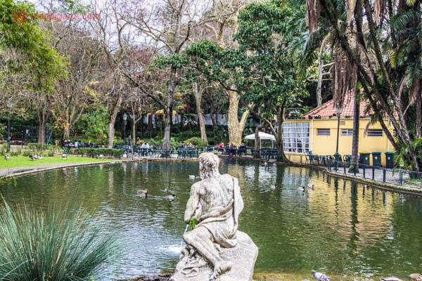O que fazer em Lisboa: O Jardim da Estrela, no bairro da Estrela, em Lisboa, é famoso por seu jardim cheio de verde, seus patos e marrecos. Uma estátua está na beira de um lago artificial, cercado de árvores verdes e outras peladas. A foto foi tirada no inverno.