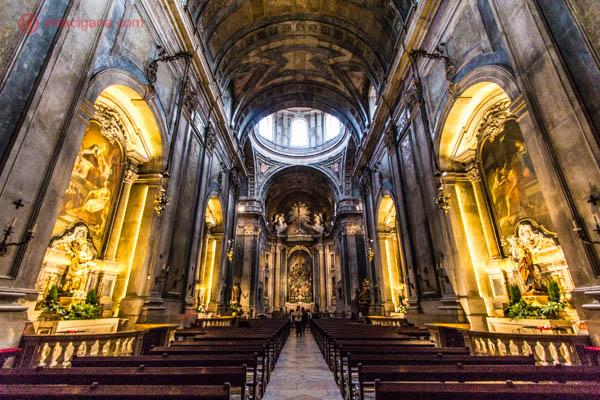 """O que fazer em Lisboa: A Basílica da Estrela, no bairro da Estrela, em Lisboa, famosa por guardar o corpo de D. Maria I, conhecida aqui no Brasil como """"A Louca"""". A igreja é lindíssima, com arquitetura barroca. Seu interior é bem rebuscado e escuro, com paredes marrons e iluminação amarelada. Uma cúpula se encontra acima do altar."""