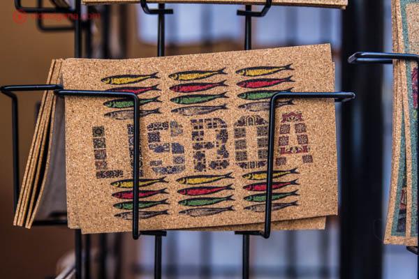 """O que fazer em Lisboa: Um cartão postal feito com papel reciclado em Lisboa. No cartão está escrito """"Lisboa"""" e vários peixinhos desenhados em volta nas cores branca, verde, vermelha e amarelo."""