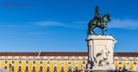 O que visitar em Lisboa: A estátua equestre de D. José I na Praça do Comércio em Lisboa, cercada de prédios amarelos de telhas ocre. O céu no dia desta foto estava incrivelmente azul.