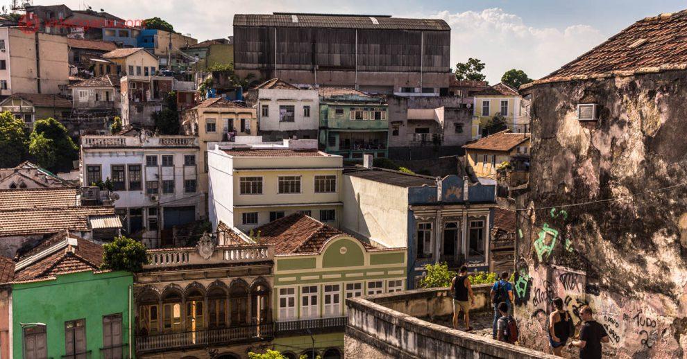 A vista da Pequena África, no Rio de Janeiro, do alto dos Jardins Suspensos do Valongo. Várias casinhas de 2 andares coloridos podem ser vistos do topo, pessoas descem pela esquina do Morro da Conceição.
