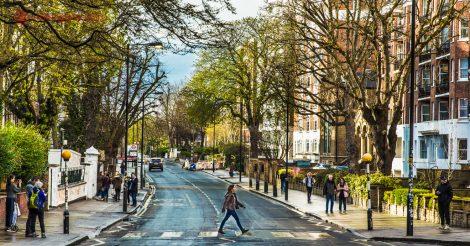 Abbey Road em Londres: Mulher cruza a famosa faixa de pedestres em Abbey Road, na capital inglesa, em um dia de sol e céu azul. Pessoas aguardam sua vez de atravessar a rua. Árvores estão dos dois lados da calçada, com prédios baixos. O asfalto está molhado.