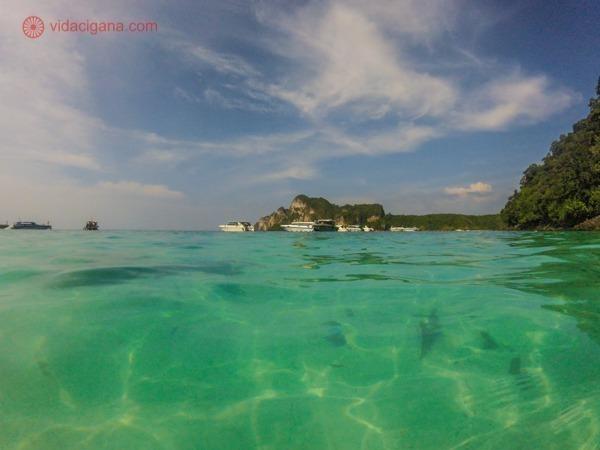 Onde ficar em Koh Phi Phi: Uma praia em Koh Phi Phi na Tailândia, com suas águas verdes transparentes. Ao fundo, iates e uma colina verde. O céu está azul com nuvens brancas.