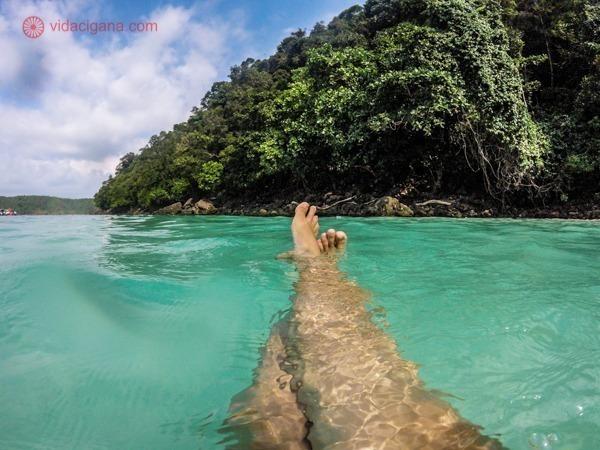 Onde ficar em Koh Phi Phi: Pernas esticadas e cruzadas dentro d'água nas Ilhas de Koh Phi Phi na Tailândia. As águas são clarissimas e transparentes, azuis. Em frente, um paredão cheio de verde. O céu está azul com algumas nuvens brancas.