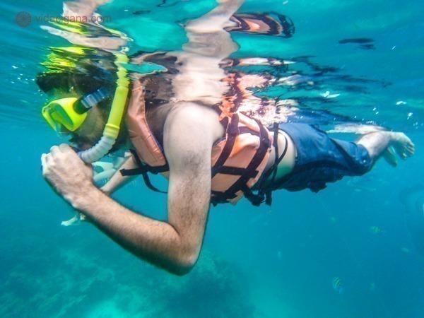 Onde ficar em Koh Phi Phi: Um homem mergulha com snorkel em Pileh Lagoon, em meio a um mar azul que parece de mentira de tão azul.