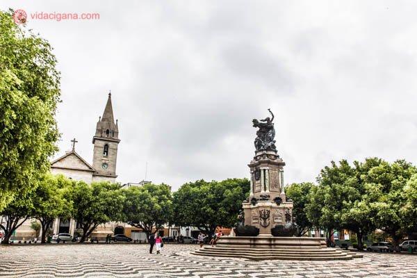 O que fazer em Manaus: A Praça São Sebastião, com sua estátua em seu meio, cercada de árvores e com a Igreja de São Sebastião a sua esquerda.