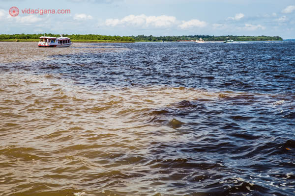 O que fazer em Manaus: O encontro das águas. a junção do Rio Negro e Solimões que irão se transformar no Rio Amazonas. O rio negro possui as águas escuras e o Solimões possui as águas barrentas. Um barquinho está parado entre as águas.