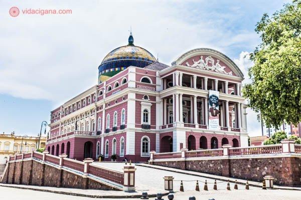 O que fazer em Manaus: O Teatro Amazonas, prédio mais famoso da cidade e do estado, surge imponente na Praça São Sebastião, com suas cores rosa e branca. Sua cúpula tem as cores do Brasil. O céu está azul e existem árvores no entorno.