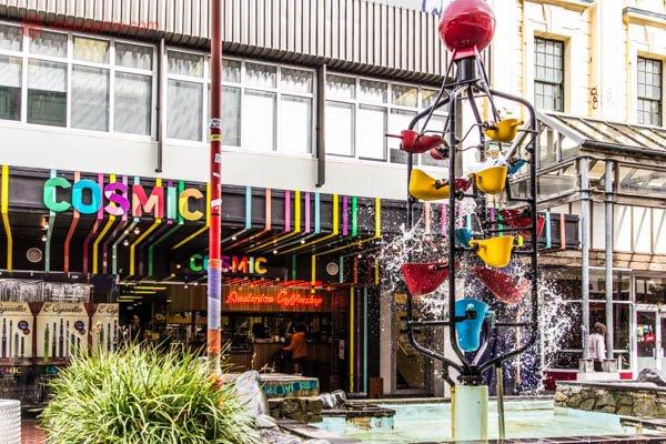O que fazer em Wellington: A Cuba Street, rua mais descolada de Wellington, cheia de lojas coloridas e descoladas, com chafarizes de baldes coloridos jorrando água.