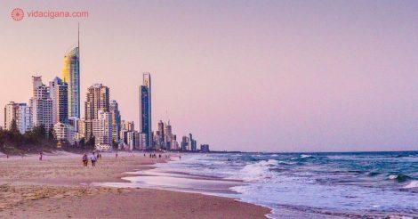 Onde ficar em Gold Coast: Surfers Paradise é o local mais badalado da Gold Coast, onde a maior parte dos turistas ficam. Pertinho do mar, a um passo da praia, cheio de hoteis e com uma noite badalada. Na foto vemos Broadbeach no pôr do sol, com seu céu roso e rosa, seus arranha-céus do lado esquerdo da foto e seu mar azul. Pessoas andam nas areias da praia.
