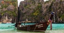 Onde ficar em Koh Phi Phi: Um longtail boat em Maya Bay, em Koh Phi Phi, ancorado na praia de areias claras e águas verdes claras e transparentes. No fundo, os icônicos paredões de Maya Bay, altos e com vegetação entre suas rochas.